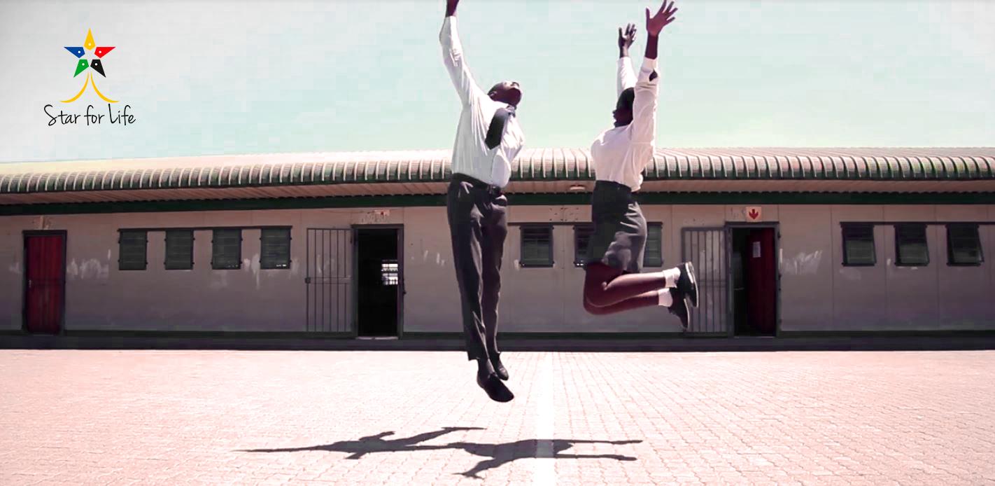 Två elever på skolan i Sydafrika hoppar glatt